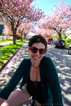 Cyclists ride beneath cherry and sakura blossoms in Vancouver.
