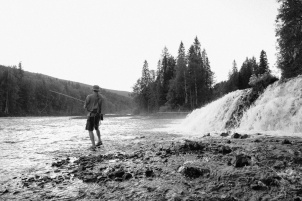 A man fishes below a waterfall in this black and white photo.