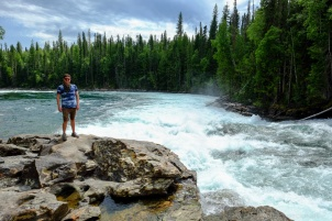 A man poses next to the whitewater of a rushing river.