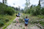 A family clears the road from fallen tree debris along a BC highway.