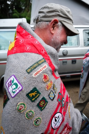 A man wearing a Scouts campfire blanket and badge collection.