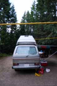 A clothes line is set up beside a Volkswagen Westfalia.