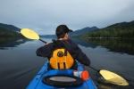A man paddles his kayaka boat on Mahood Lake, Wells Gray Park.