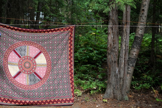 A patterned textile hangs in the trees.