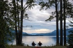 A couple reads beside Mahood Lake, Wells Gray Park, BC.