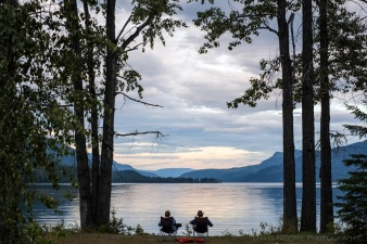 A couple reads beside Mahood Lake, Wells Gray Park, BC.