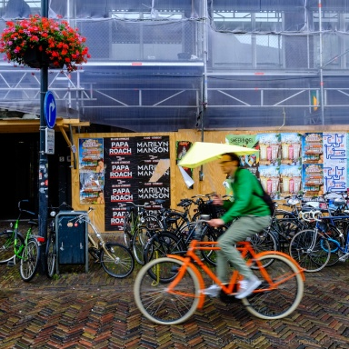 A man cycles with an umbrella in the rain, in Delft.