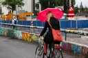 A woman covers up with an umbrella while cycling in the rain in Utrecht, Netherlands.