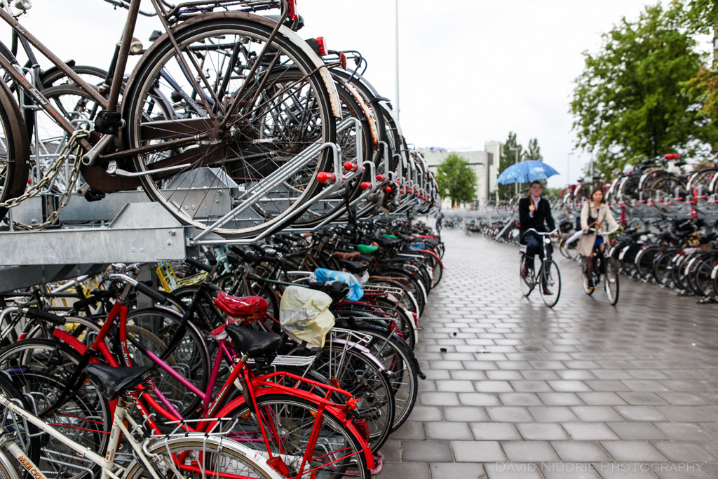 Cyclists ride past bike parking in Utrecht, Netherlands on a rainy day.