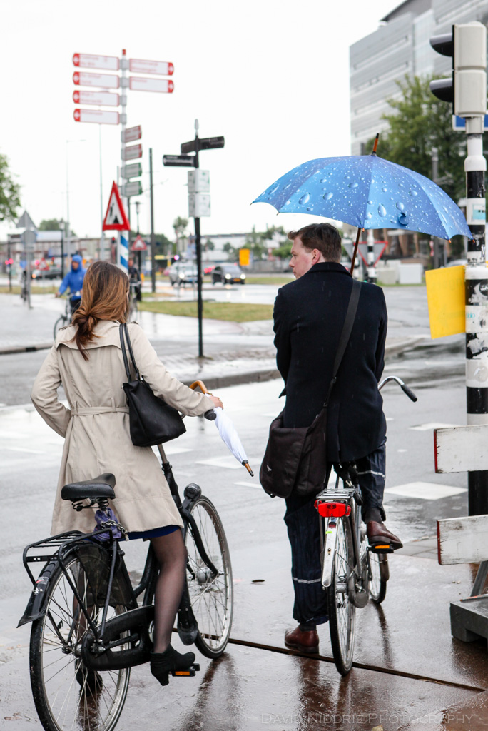 A couple stops at a light while cycling in the rain in Utrecht, Netherlands.