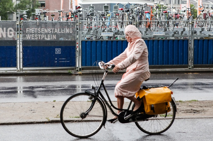 A woman covers up with a poncho while cycling in the rain in Utrecht, Netherlands.