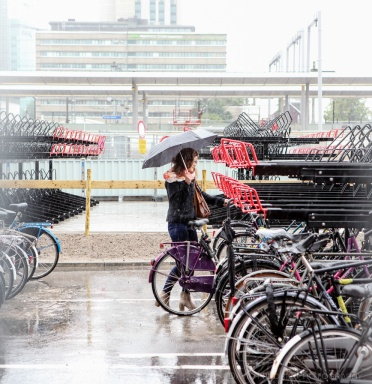 A woman parks her bicycle in the rain in Utrecht, Netherlands.
