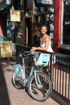 A woman walks through Gastown, Vancouver with a Mobi bike share bicycle