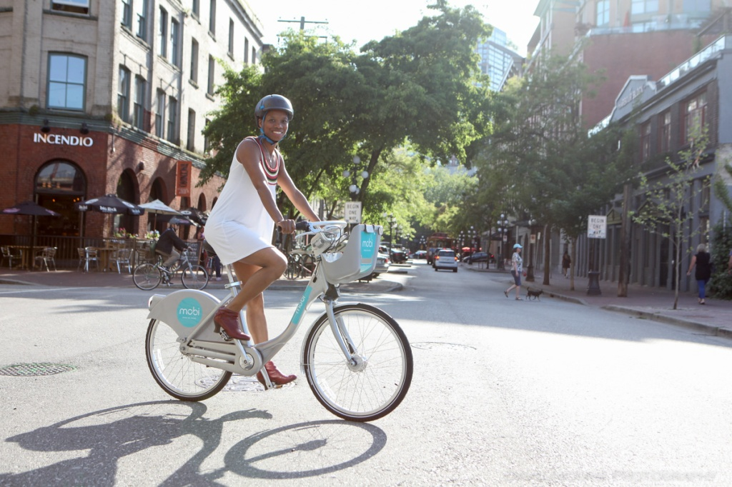 A woman rides through Gastown, Vancouver on a Mobi bike share bicycle