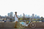 A woman looks out over Vancouver city with a Mobi bike share bicycle by her side.