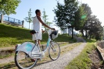 A woman walks through CRAB Park, Vancouver with a Mobi bike share bicycle