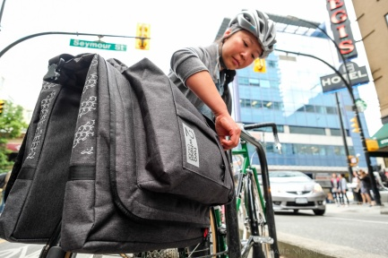 A woman poses on a Vancouver street with Two Wheel Gear bicycle pannier.
