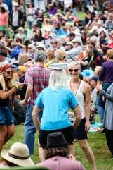 A man blanaces a book on his head while dancing at the Folk Festival.