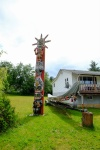 A totem pole stands outside the residence of a local Chief.