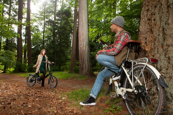 A couple meet in the forest to ride their e-bikes together